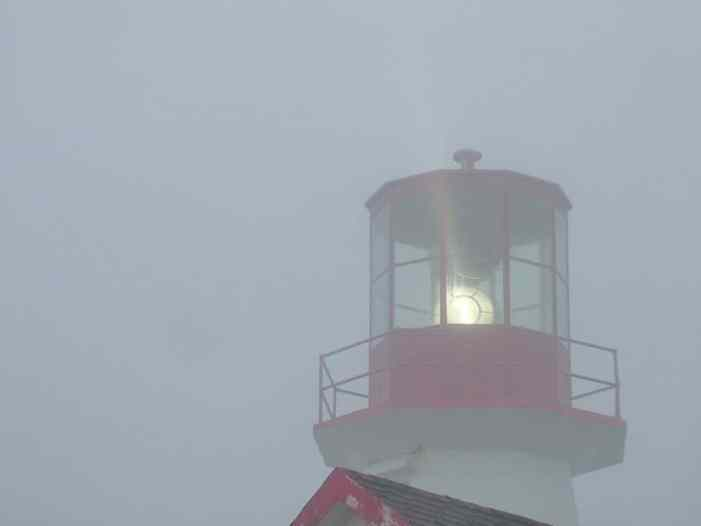 lighthouse beaming light through fog, quirpon island, newfoundland, canada