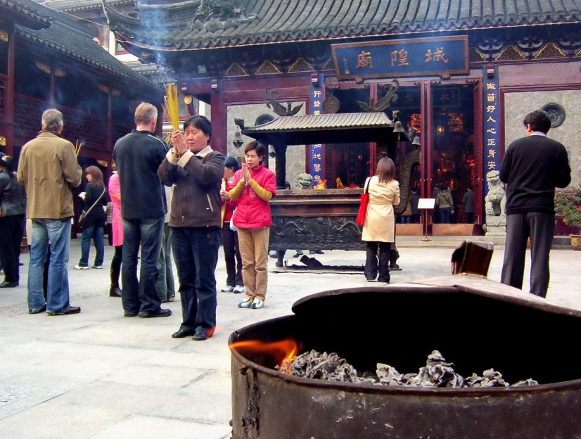 People pray to the gods will holding incense sticks inside the City God Temple of Shanghai.