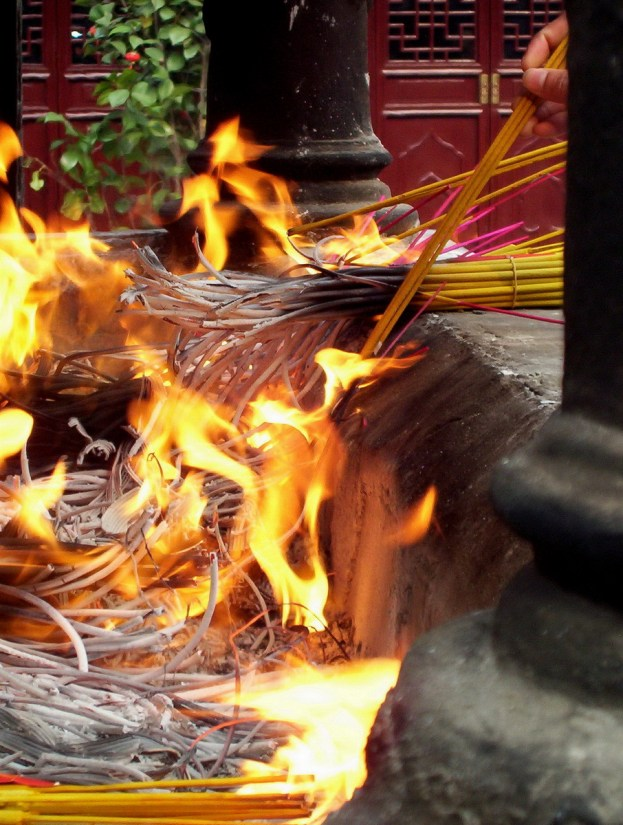 Burning incense sticks in the burning pit inside the City God Temple of Shanghai.