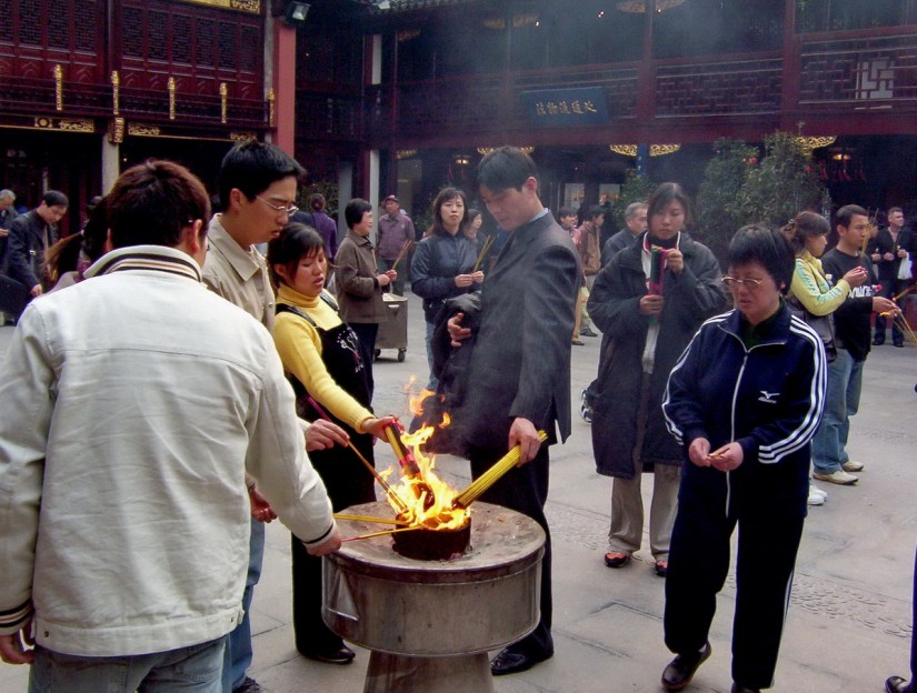 People lite their incense sticks in the main courtyard of the City God Temple of Shanghai in China.