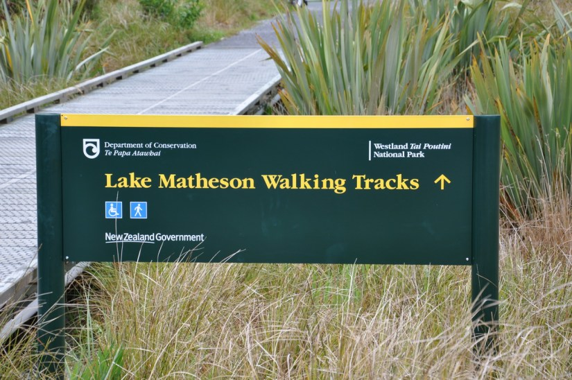 a sign for lake matheson walking tracks, south island, new zealand