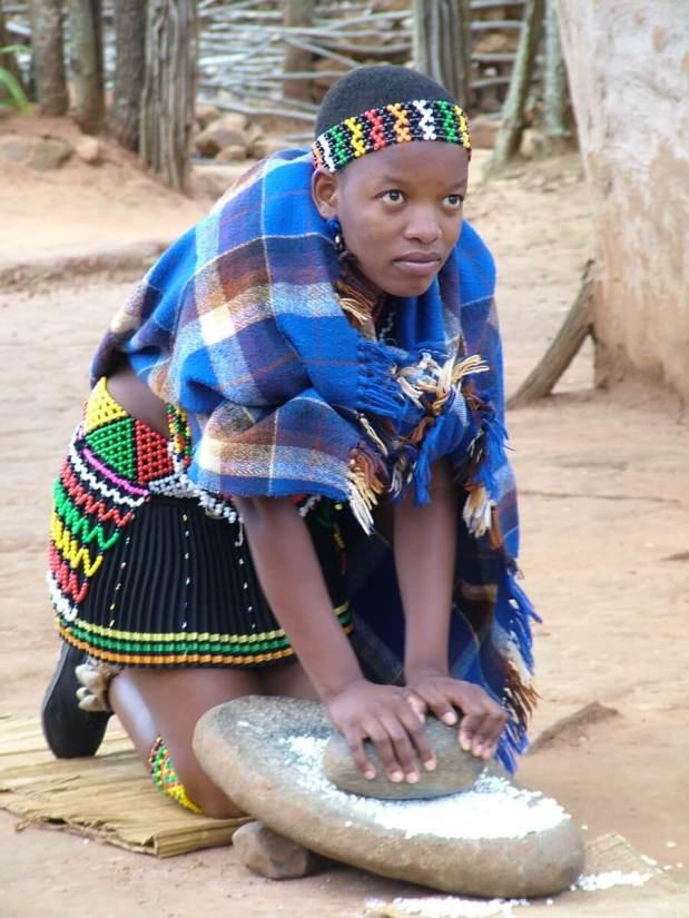 a zulu maiden grinding grain, shakaland, kwazulu-natal, south africa