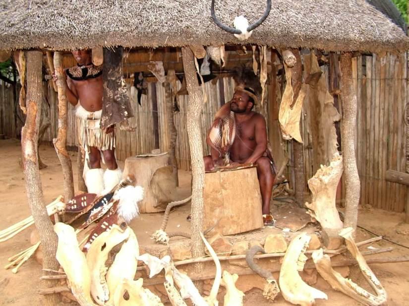zulu men in a shelter with animal bones, shakaland, kwazulu-natal, south africa