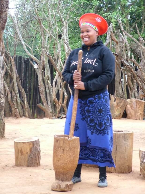a married zulu woman grinding sorghum, shakaland, kwazulu-natal, south africa