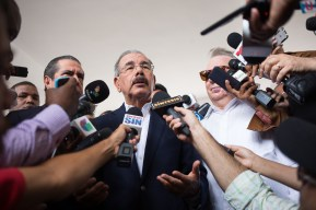 DOMINICAN REPUBLIC, Santo Domingo : Dominican President and presidential candidate for the Democratic Liberation Party (PLD), Danilo Medina (C), speaks to the press after voting at a polling station in Santo Domingo during general elections on May 15, 2016. Voting began Sunday in the Dominican Republic's presidential election, where incumbent leader Danilo Medina is tipped to win despite grinding poverty and widespread crime. / AFP PHOTO / Fran Afonso