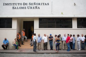 DOMINICAN REPUBLIC, Santo Domingo : People wait in line outside a polling station during general elections in Santo Domingo on May 15, 2016. Voting began Sunday in the Dominican Republic's presidential election, where incumbent leader Danilo Medina is tipped to win despite grinding poverty and widespread crime. / AFP PHOTO / Fran Afonso