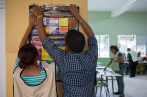 DOMINICAN REPUBLIC, Santo Domingo : People paste a poster with electoral information at a polling station during general elections in Santo Domingo on May 15, 2016. Voting began Sunday in the Dominican Republic's presidential election, where incumbent leader Danilo Medina is tipped to win despite grinding poverty and widespread crime. / AFP PHOTO / Fran Afonso