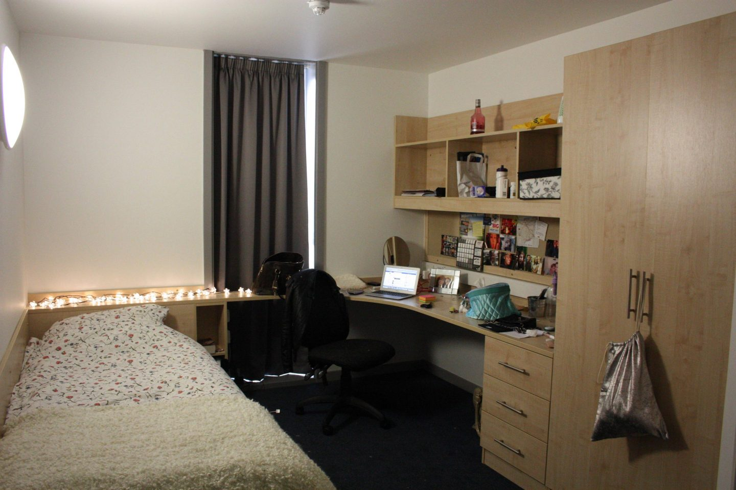 a photograph of a university dorm room; a floral duvet sits on a bed covered by a fluffy white blanket, white fairy lights just above it; a desk chair sits at a desk with a macbook on a table, in front of a noticeboard full of photographs
