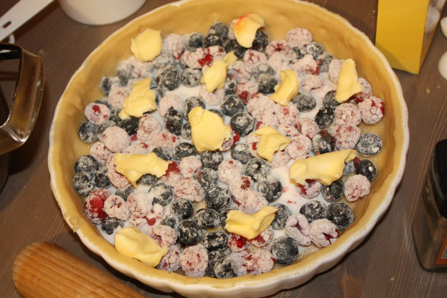 a freshly rolled pie dough in a pie dish, filled with blueberries, raspberries, butter, and sugar