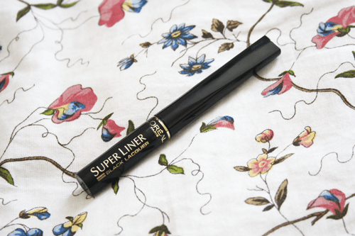 l'oreal super liner black vinyl packaging and review; l'oreal super liner in black laquer lying on a bed