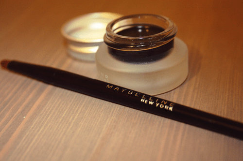 Maybelline Eye Studio Lasting Gel Liner and brush lying on a table; the eyeliner is in a glass pot, with the lid removed