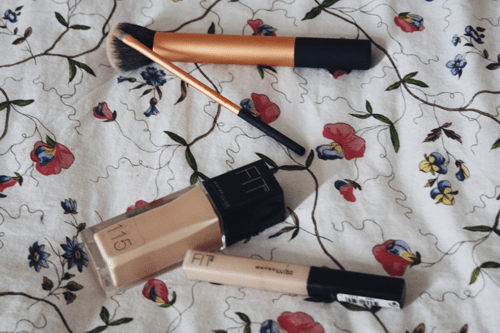 maybelline fit me foundation and concealer side by side on a bed next to real technique buffing and concealer brushes