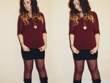 blogger francesca sophia stands against a cream wall, wearing a burgundy oversized jumper, a black body con skirt, a pair of knitted burgundy tights and black boots
