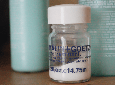malin + goetz acne treatment sitting on a wooden dressing table, with several Clinique lotions sitting behind it; the formula has separated, so a white powder sits on the bottom, and a clear liquid sits on top.
