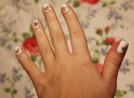 francesca sophia's hand, with white polish on her finger nails and pink glittery hearts painted on each one