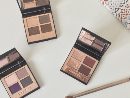 Charlotte Tilbury Colour-Coded Eyeshadows in glamour muse, golden goddess, and vintage vamp, lying open on a dresser, next to an urban decay eyeshadow brush