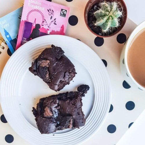 Vegan Oreo Brownies recipe on francescasophia.co.uk | a plate of vegan oreo brownies sitting on a polka dot notebook, next to a cup of tea, cactus, and two packets of tea