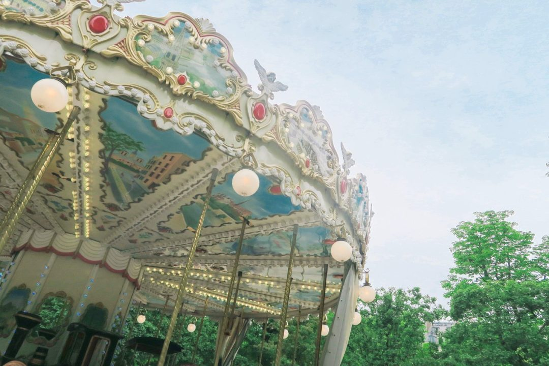 The underside of a carousel with a view of the sky A row of Parisian houses on Monmarte in day trip to Paris on a budget on francescasophia.co.uk