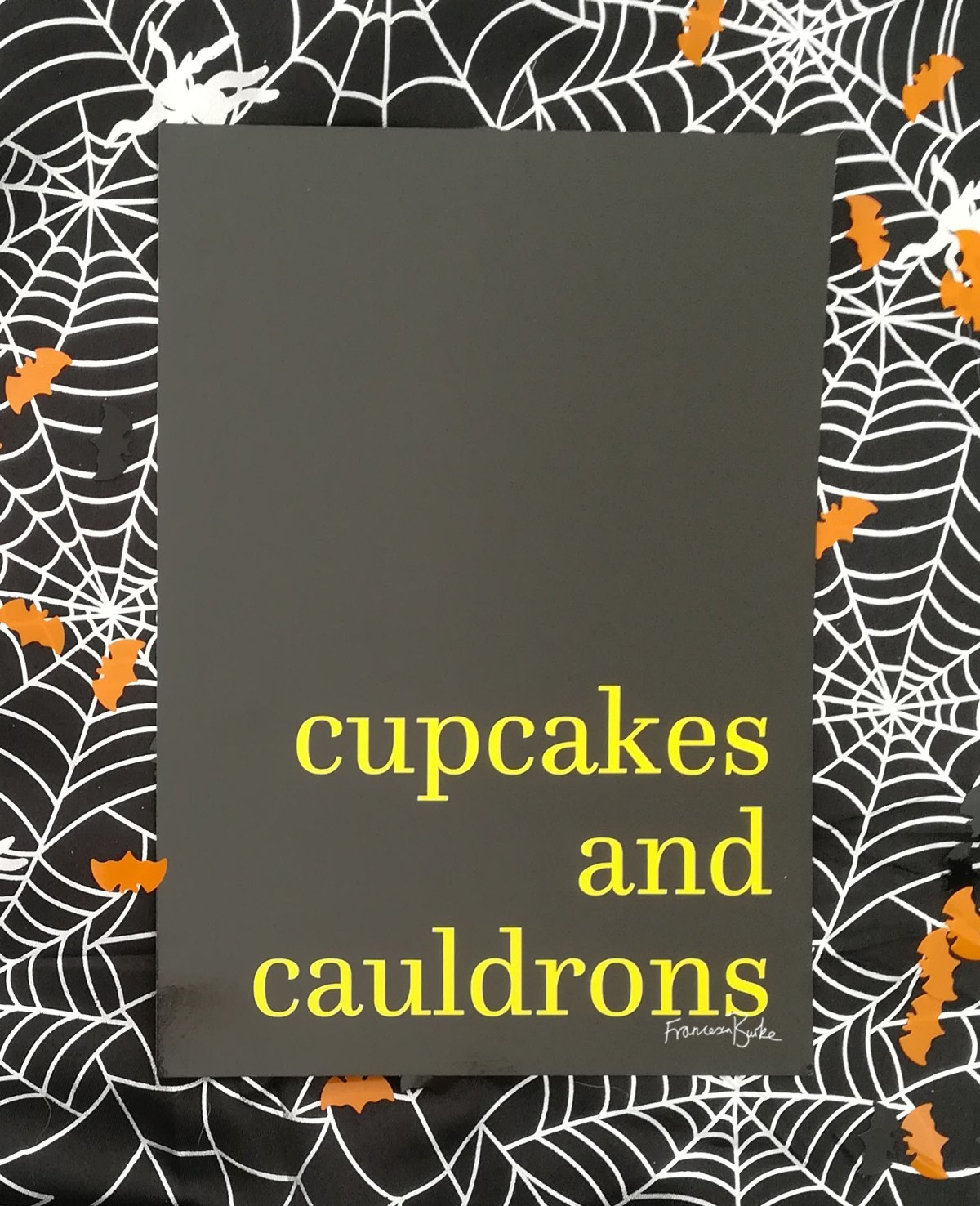 black and yellow print reading 'cupcakes and cauldrons'