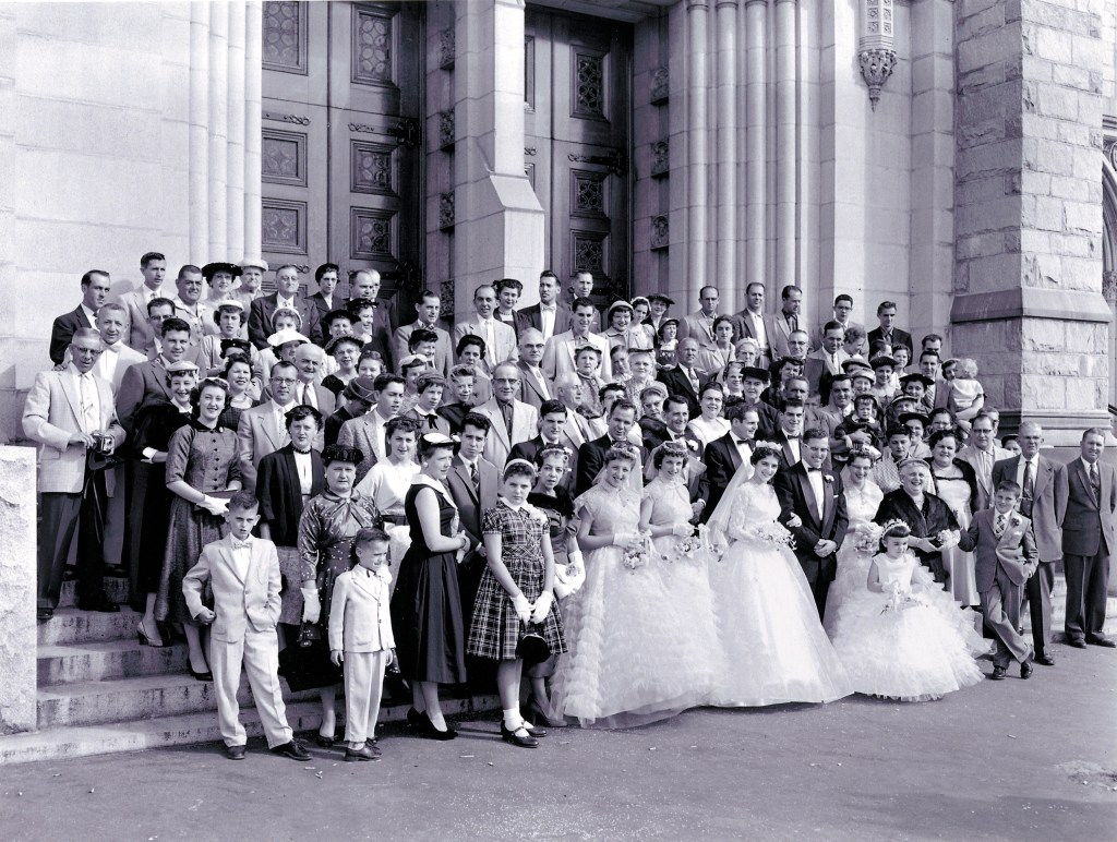This photo shows multiple families posing for wedding portraits together. The photo is unknown.  Three brides are featured with many family members standing on the steps behind them.