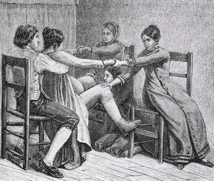 A black and white wood print made by Gustave-Joseph Witkowski 1887.  Image depicts a birthing scene.  The woman giving birth is sitting being braced by three others with the midwife helping the birth.