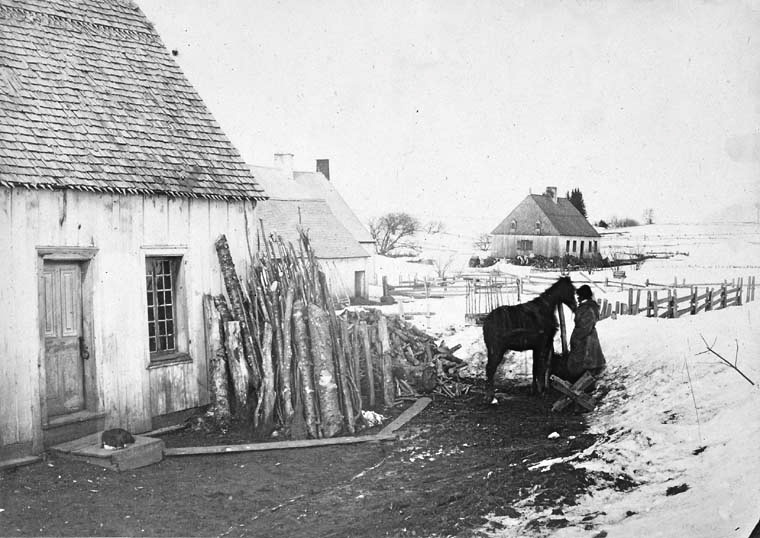 """Black and white photo taken by Samuel McLaughlin, titled """"Winter Scene in Canada"""" taken in 1859.  It features a woman standing close to a horse next to a house in the winter."""