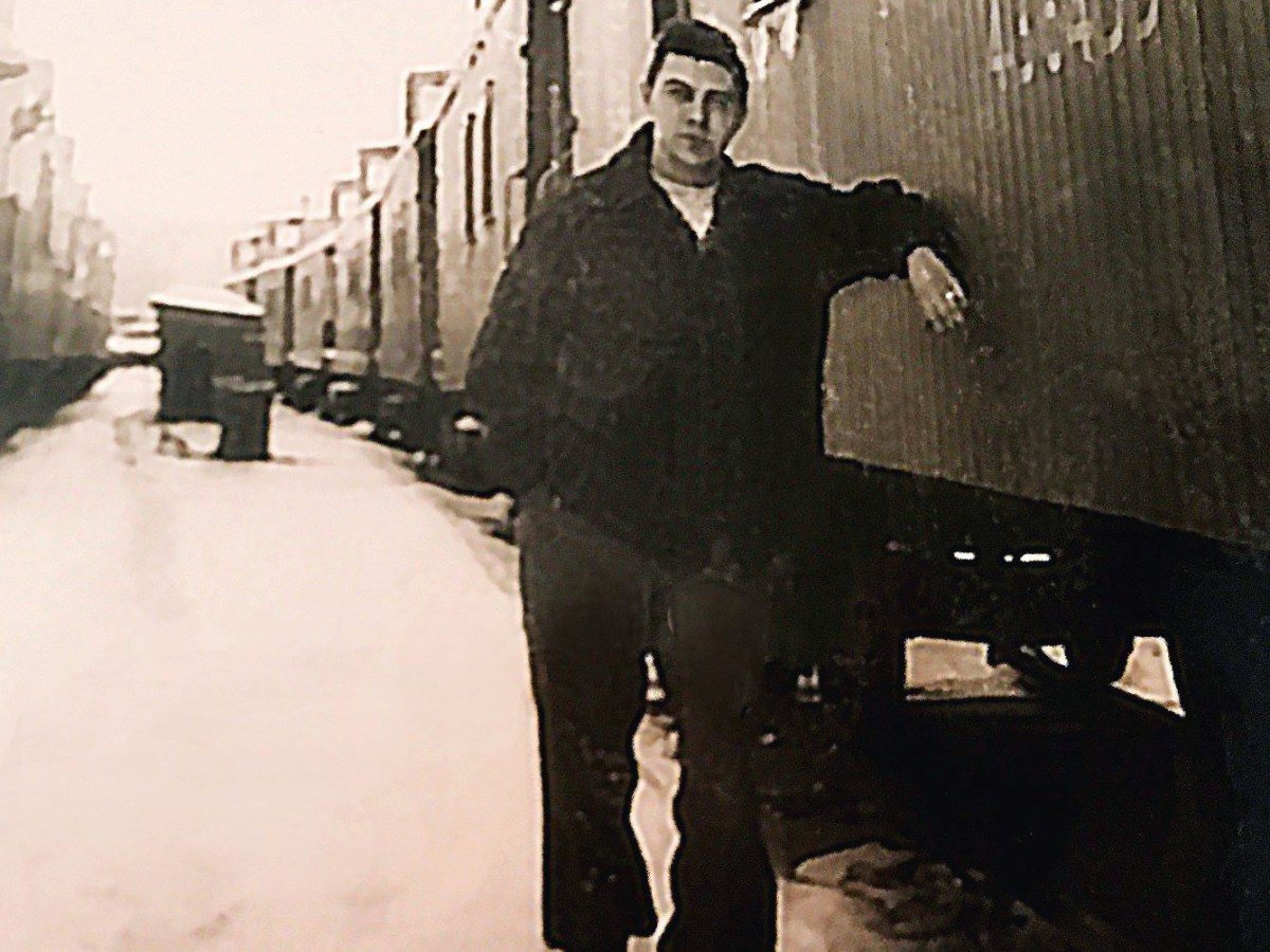 This is a picture of Armand Vachon as a young man. He is leaning on a rail-car in a black and white photo.