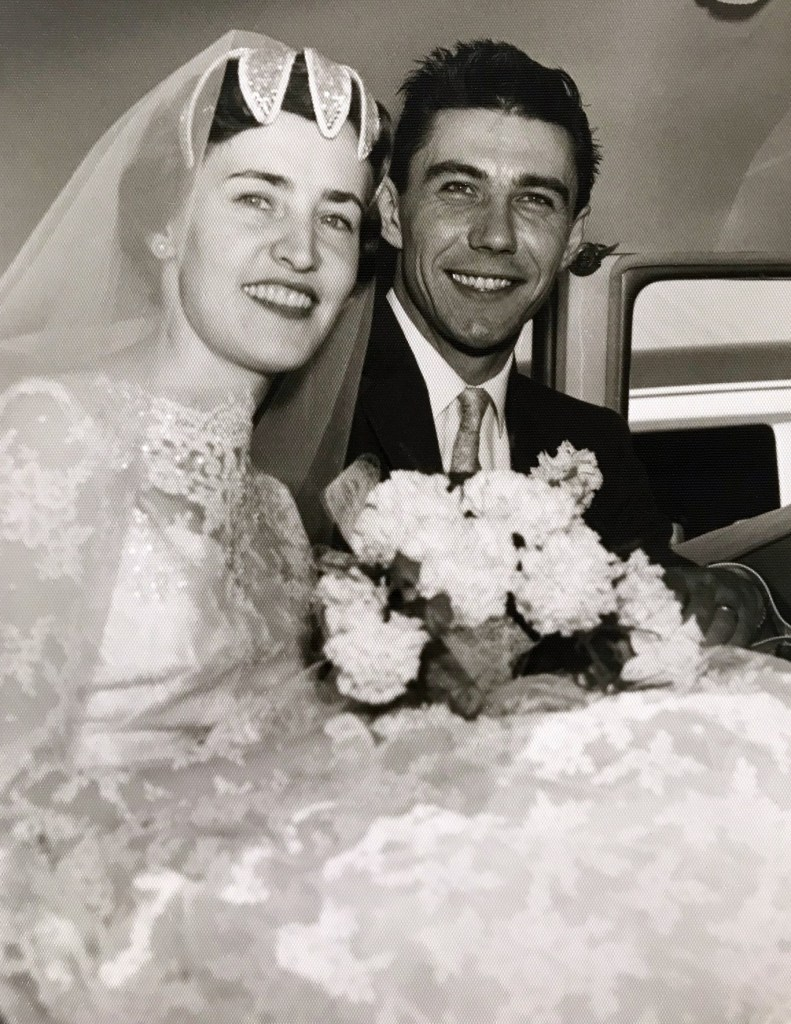 This is a black and white picture of Armand and Lucette on their wedding day in the back of a car. They are both smiling.