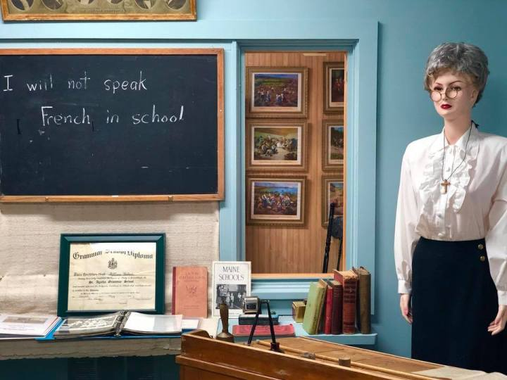 Photo of a school house exhibit with I will not speak French in school written on the chalk board.