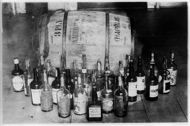 Photo taken during prohibition era of confiscated whiskey bottles and barrels.