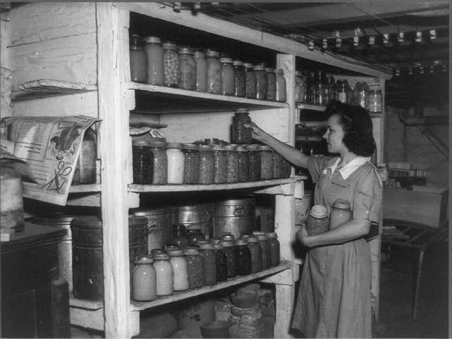 Black and white photo of a woman stacked home canned goods in her cellar