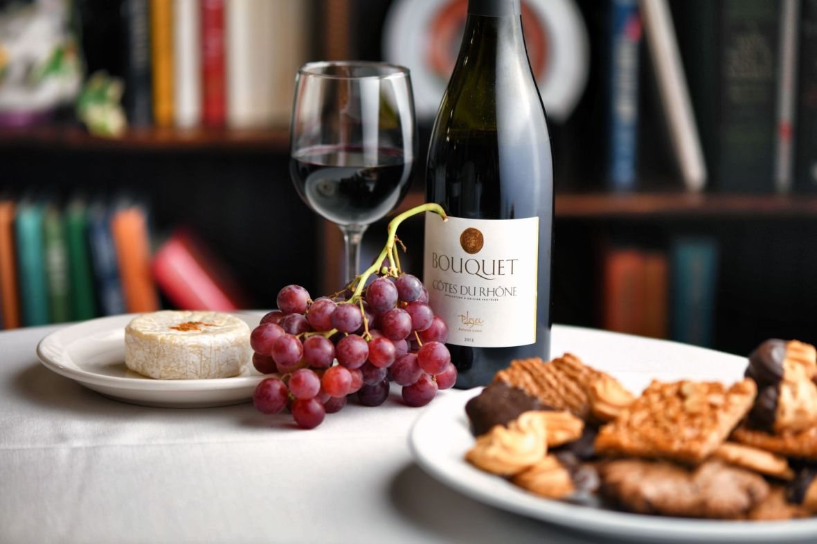 Red grapes, brie cheese, Cotes Du Rhone, plate of assorted cookies. French cuisine
