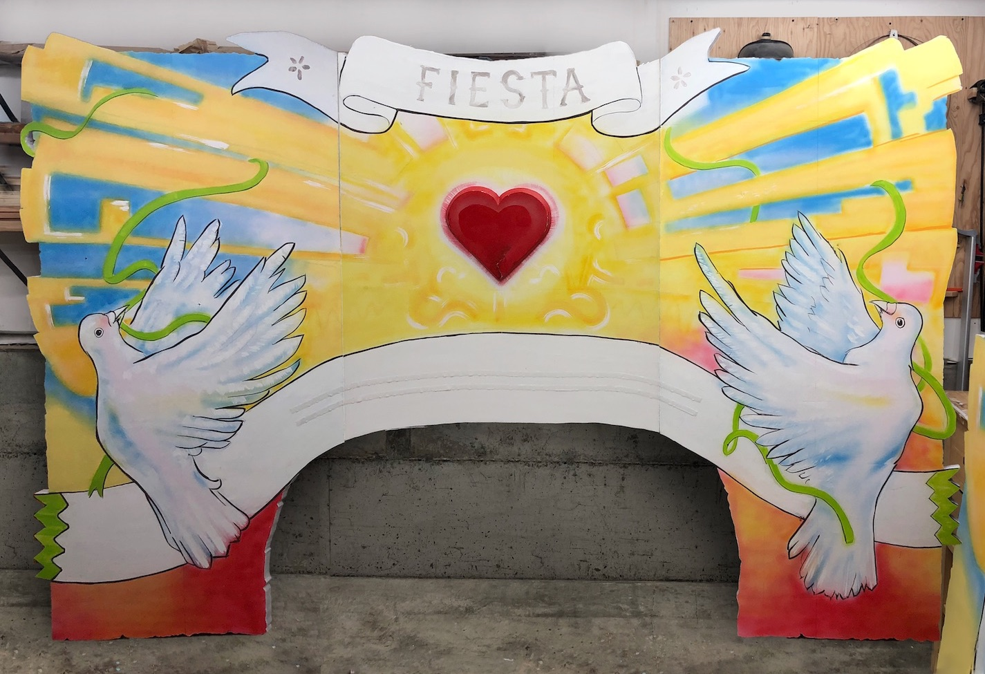 Twelve-foot wide arch painted with doves and banners around a heart.