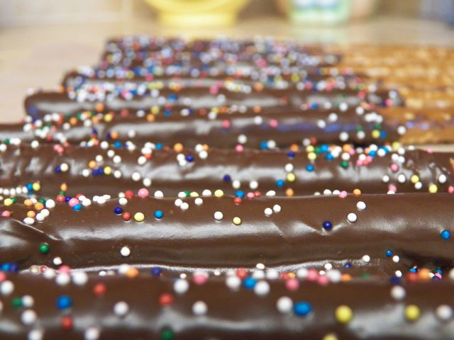 Pretzel rods dipped in melted dark chocolate and decorated with nonpariel candies.