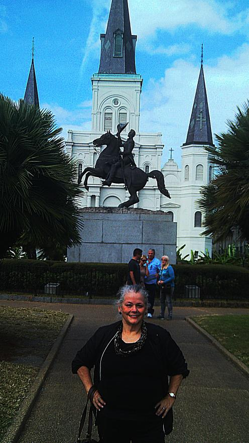 My mother poses in front of the statue of the Hero of New Orleans who fought the British Empire and become President and the Church of the Sainted Crusader King.