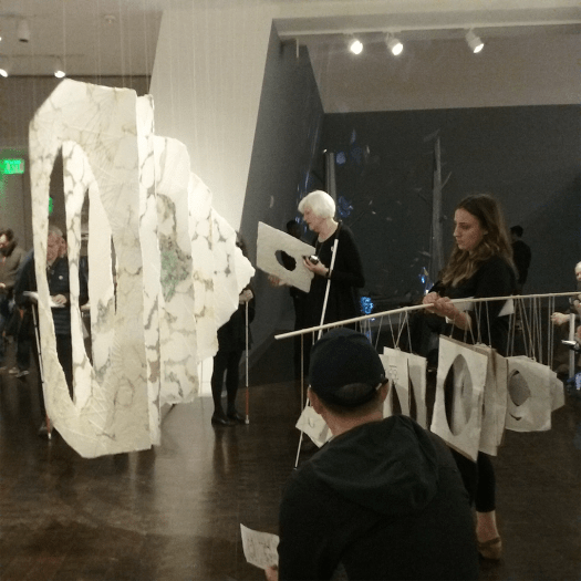 Sheets of exquisite and handmade paper with complex textures, pale colors and central holes hang from the ceiling in a row. A tall woman with white hair and white cane holds a piece of paper. A woman to her right holds a pole with a smaller version of the sculpture. In the background a woman reads from a Braille folder and several people holding canes listen to the conversations.