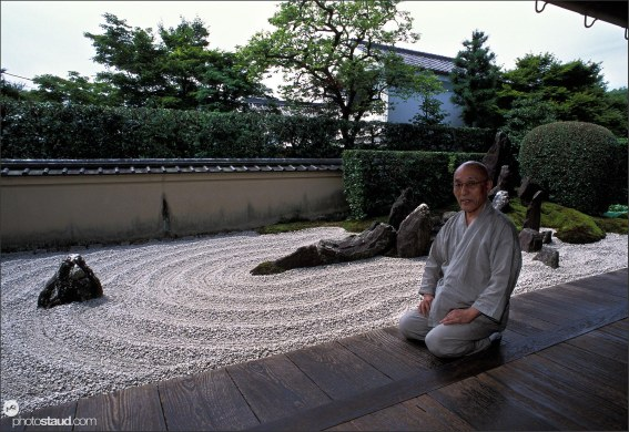 Japanese Buddhist monk sitting on the veranda of Zuiho-in Temple with Zen Garden behind, Kyoto, Japan