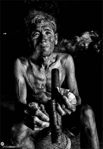 Khumhi, about 80-year old head-hunter lives in the village of Longwa and spends most of the day chewing betel nuts and smoking opium.