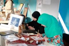 Mitarbeiterinnen des Islamischen Zentrums fertigen Kalligrafien. Foto: Kathrin Erbe