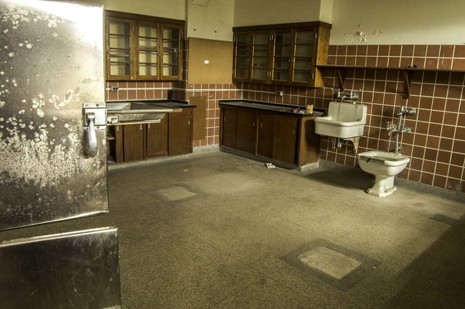 A morgue in an abandoned/vacated psychiatric hospital. The two squares on the floor are where the autopsy tables would have been. To the left are the open doors to the freezer.