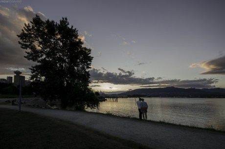 A couple in Vancouver looking through their sunset photos