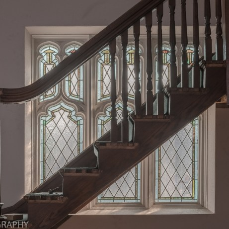close crop urban exploration photo of a stained glass window and stairs in an abandoned ontario church