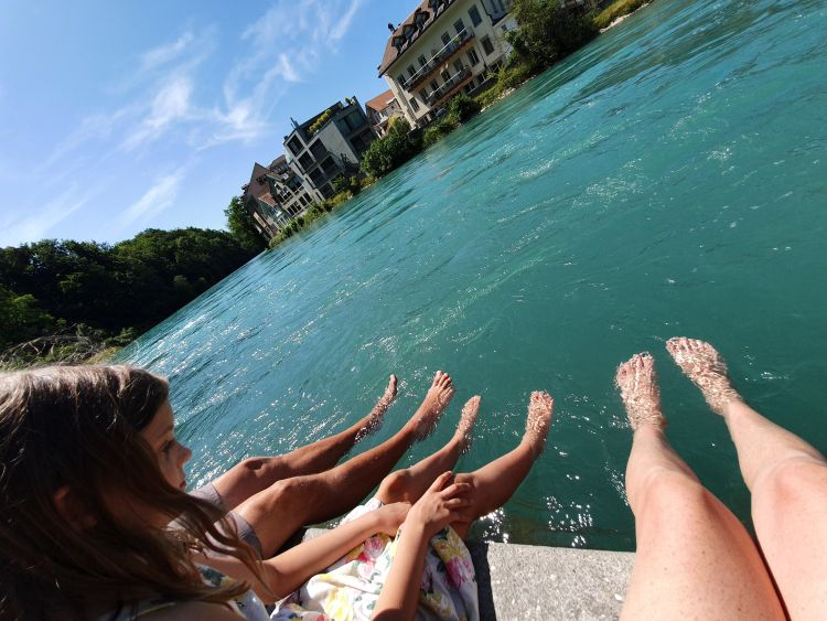 Family of three dipping their toes in the Aare River in Bern, Switzerland.