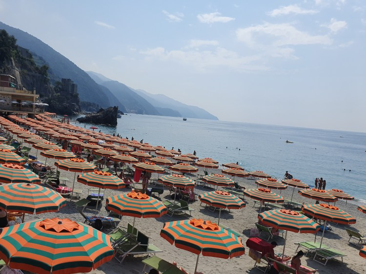 Orange and green striped umbrellas symmetrically line the beach near Monterosso in Cinque Terre, Italy