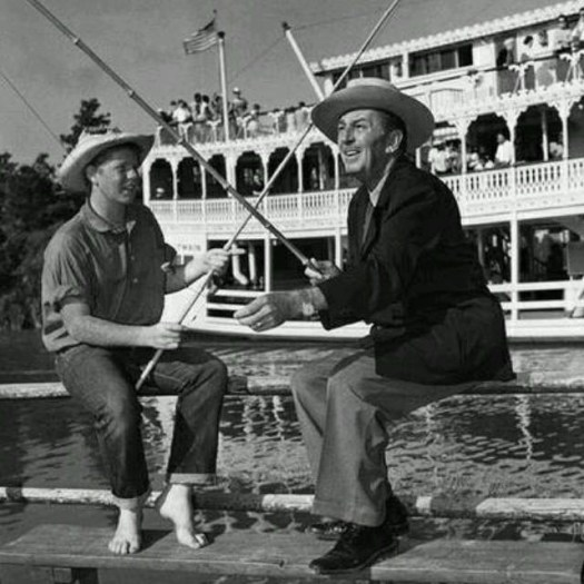 Tom Nabbe and Walt Disney fishing at Disneyland along the Rivers of America. Mark Twain steamship in background.