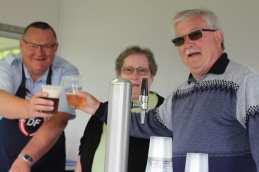 Lokalformand Gunner Nielsen og kasserer Flemming Hansen skåler i ølvognen mens frivillig Ellen Rasmussen ser til.