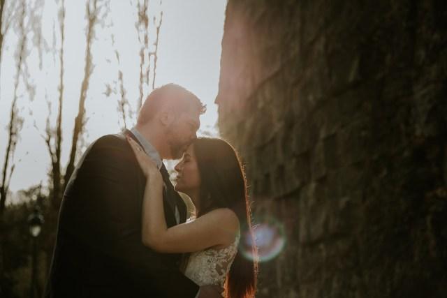 """couple mariés s""""embrassant au coucher de soleil"""