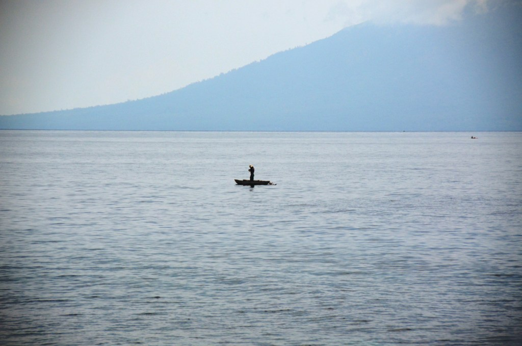 Fisherman with Manam volcano in the background