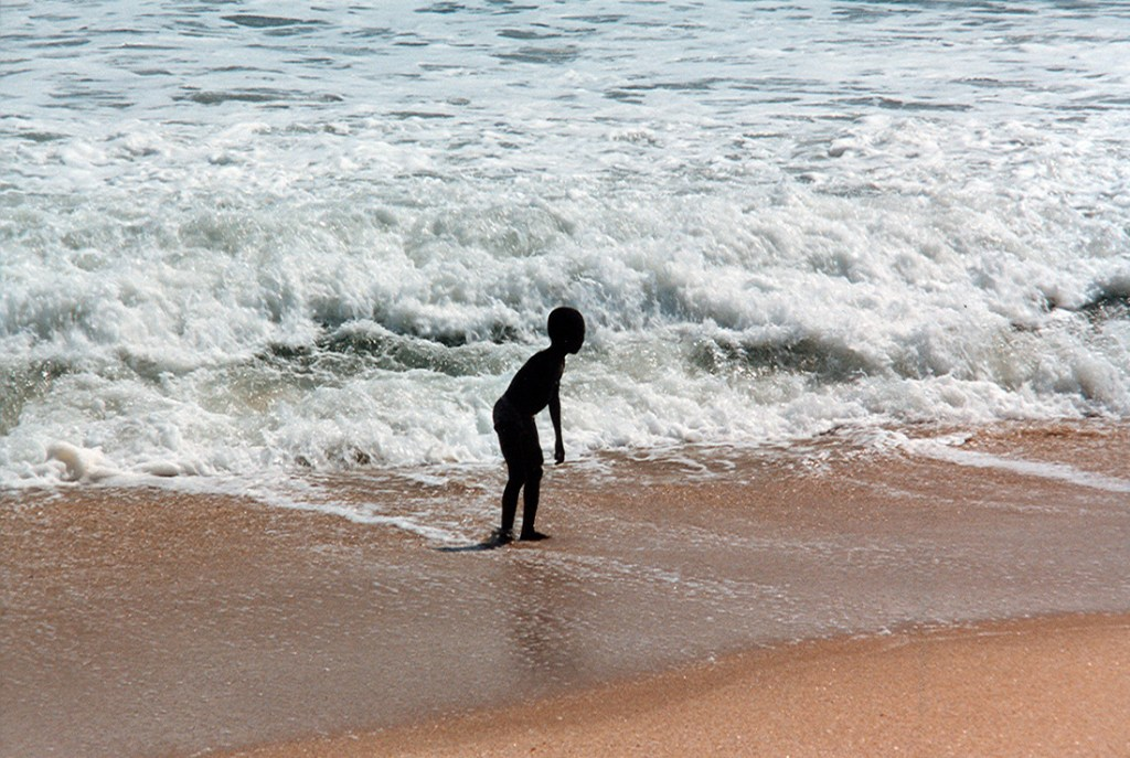 Kid playing on the beach on the gold coast in Ghana 1997