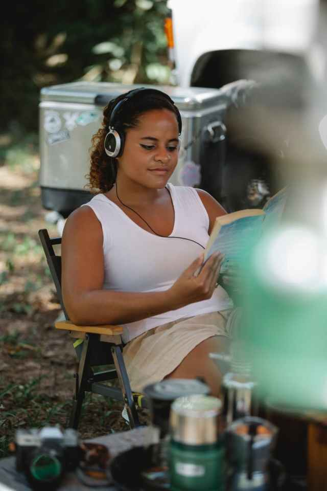 calm hispanic woman reading book while sitting in camping area in nature